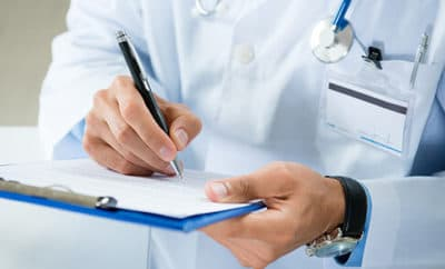 Doctor writing patient medical diagnosis