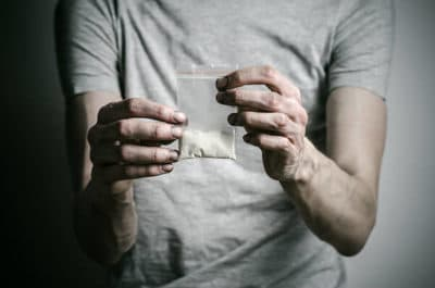 Person holding a clear bag of PCP powder