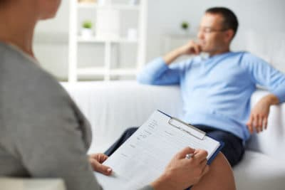 Therapist taking notes on patient mental illness