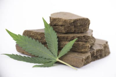 Stack of hashish blocks with marijuana leaf