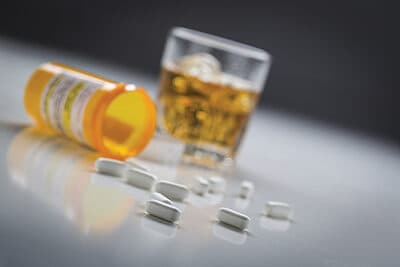 Several Prescription Drugs Spilled From Fallen Bottle Near Glass of Alcohol