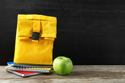 Lunch bag with food for schoolchild and notebooks on dark background